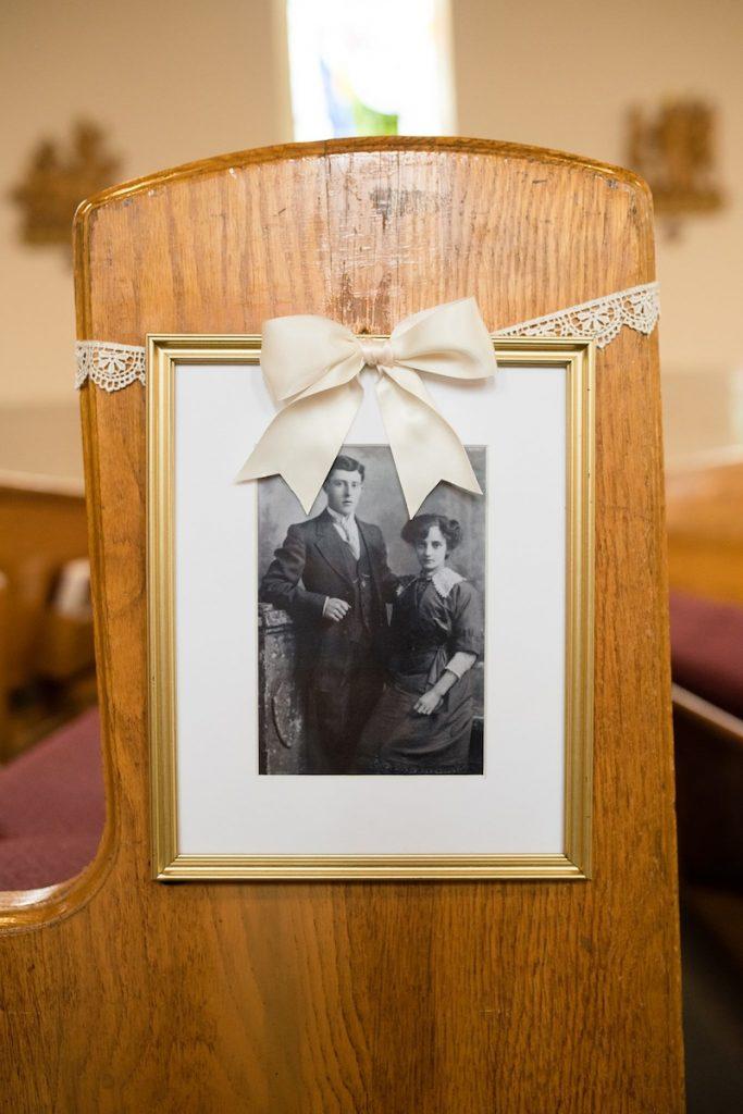 use old family wedding photos on church pews as ceremony decor