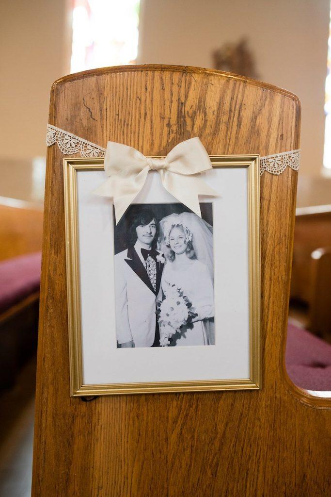 church aisle lined with framed family wedding photos instead of flowers as ceremony decor