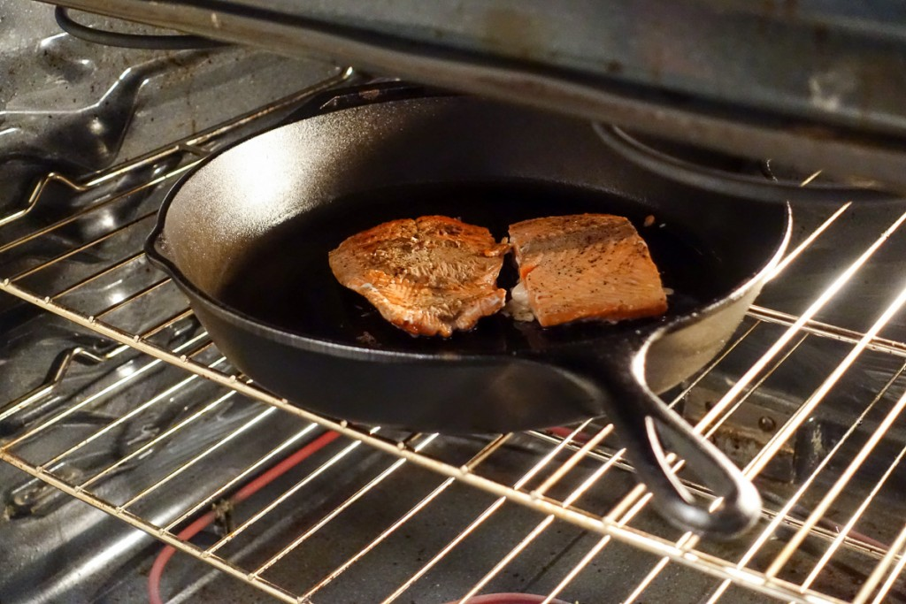 Cast iron pan with salmon in oven