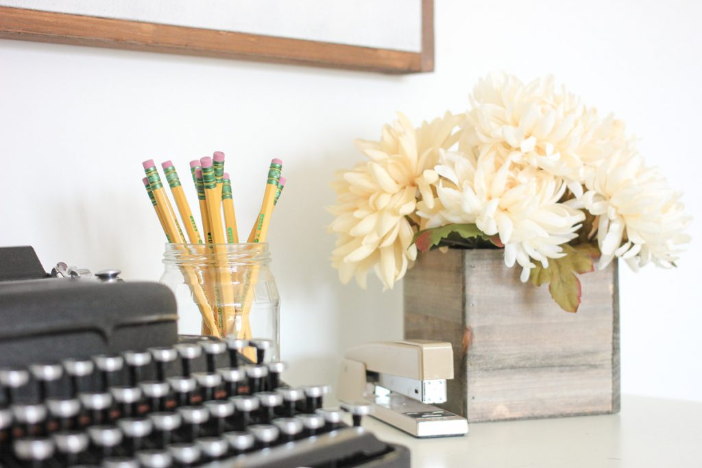 home office decor - typewriter, stapler, pencils and flowers