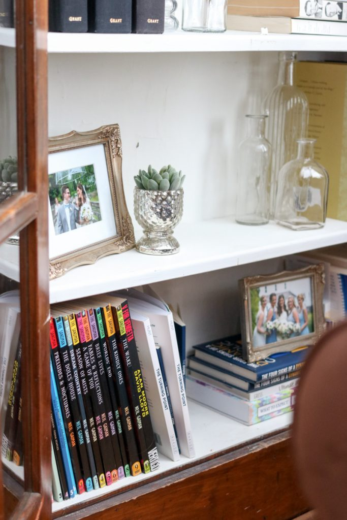 Simple, budget-friendly living room built-in bookcase styling   How I styled my 1925 craftsman house living room cabinets with objects I already owned   antique books, vintage-feel framed wedding photos, antique bottles and mercury glass votives all come together to create a vintage vibe in these built-in cabinets   Crazy Together blog #homedecor #decor #farmhouse #farmhousedecor #craftsmanhouse