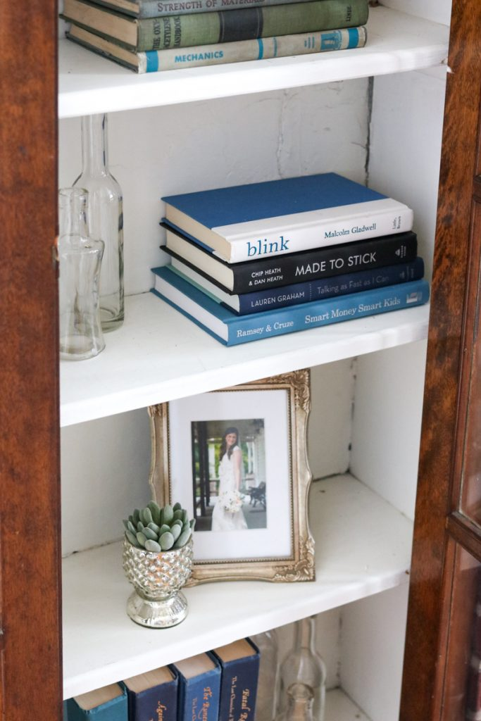 Simple, budget-friendly living room built-in bookcase styling | How I styled my 1925 craftsman house living room cabinets with objects I already owned | antique books, vintage-feel framed wedding photos, antique bottles and mercury glass votives all come together to create a vintage vibe in these built-in cabinets | Crazy Together blog #homedecor #decor #farmhouse #farmhousedecor #craftsmanhouse