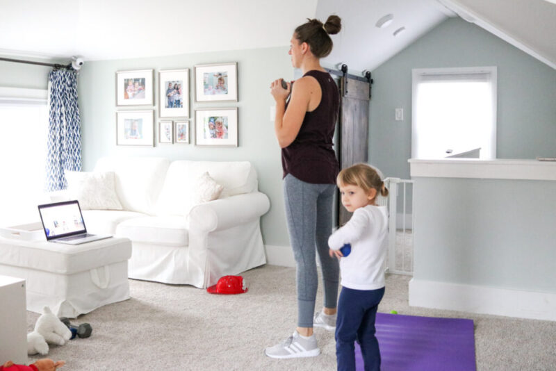 mother working out at home with young child nearby