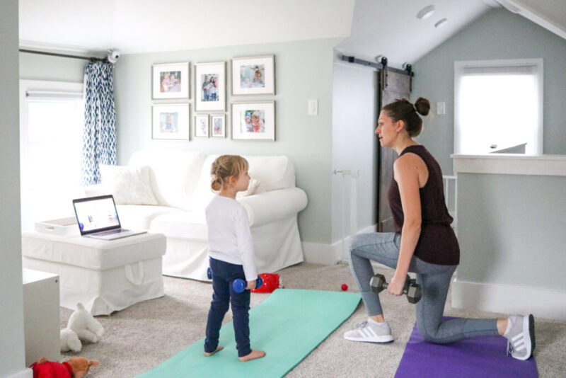 mom holding weights and working out at home with daughter