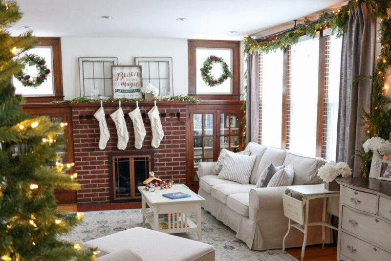 Looking for some neutral Christmas decor inspiration? Stop by to take a peek at our cozy living room decorated for the holidays. Our 1920s living room decor features hardwood floors, built-in cabinets around the mantle with simple fresh greenery and warm white LED lights. Ivory knit stockings adorn the fireplace to complete the look, which tie pin perfectly to the light beige slipcovered sofa, chair and ottoman from the Ikea Ektorp line.