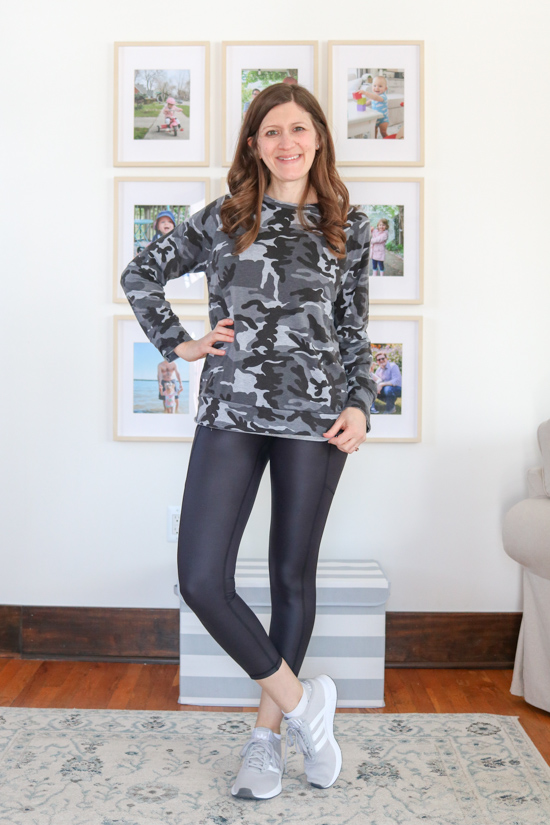 woman wearing gray camouflage long sleeve top with shiny black leggings and gray sneakers