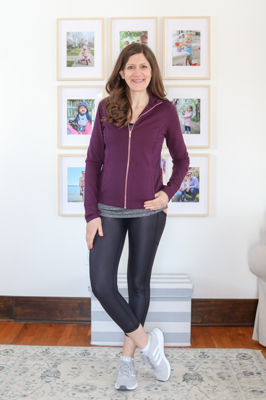 woman wearing blackberry wine colored contour zip-up jacket and shiny black leggings from Wantable Active Edit
