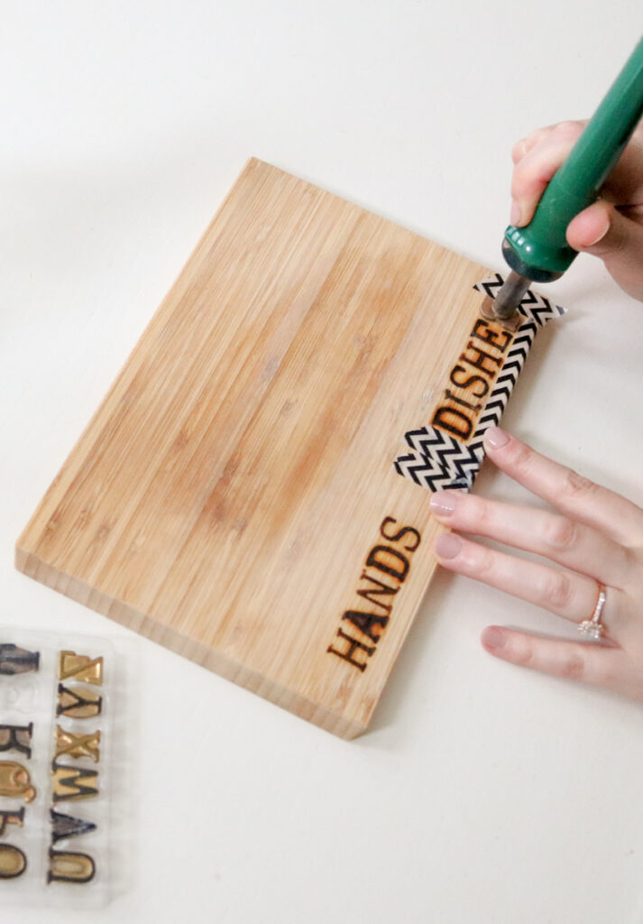 using woodburner and hot stamps to burn HANDS and DISHES labels onto hand soap dispenser tray