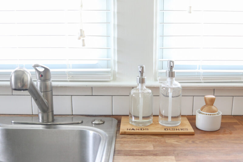 Glass kitchen soap dispensers resting on a wood tray with woodburned HANDS and DISHES labels