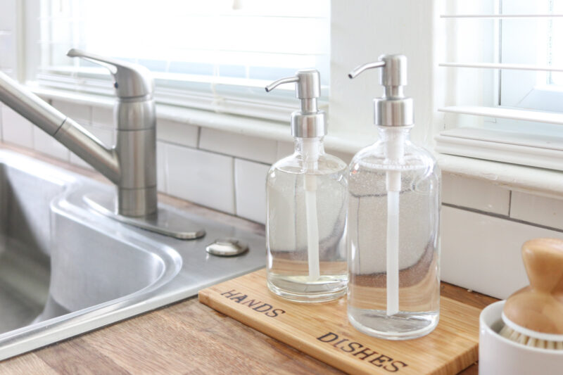 glass soap dispensers resting on a wood tray with woodburned HANDS and DISHES labels beside kitchen sink